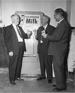 Dean John H. Longwell, an unidentified man, and Loren A. Gafke pose with milk from the Department of Dairy Science's creamery in 1955.