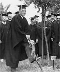 A Male Graduate Uses a Spade to Plant a Tree