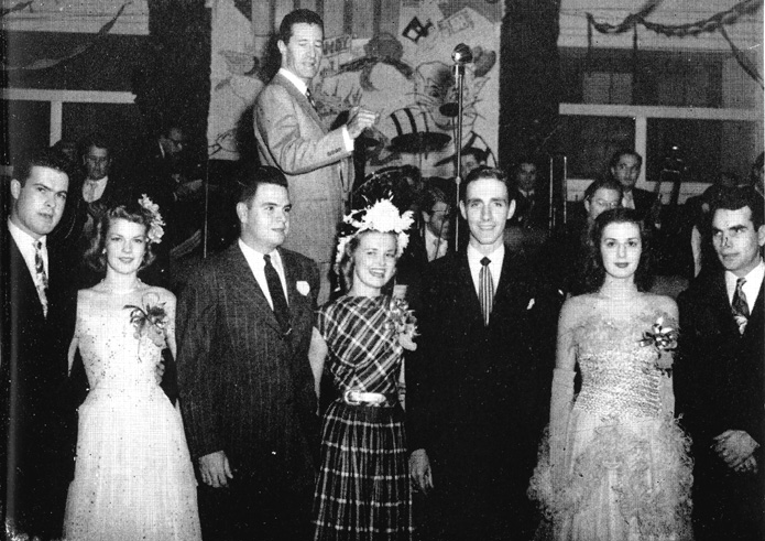 Queen Peggy Field, and her Entourage Pose in Front of Band Leader, Ray McKinley at the 1947 Homecoming Dance