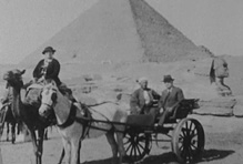 Accompanied by a guide, Sara Lockwood Williams and Walter Williams, President of the University of Missouri, stop in front of the Sphinx with the Pyramid of Khufu in the background. Still image from 16mm film, 1933.